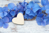 blue flower and wooden heart lying on wood