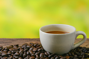 Coffee cup and coffee beans on table with nature background