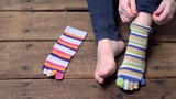 Female feet and hands putting on odd striped toe sock on the wooden floor. Closeup view