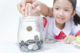 Asian little girl in Thai student uniform putting coin to glass