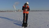 Worker with snow showel on snow covered field near factory