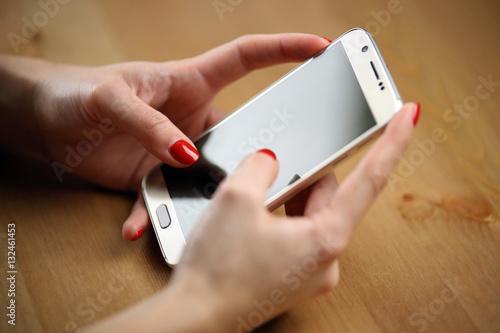 Smartphone tactile avec main d'une jeune femme vernis rouge sexy sur son télépho Poster