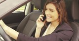 Gorgeous woman laughing on the phone in car