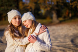 Twins sisters hugging. Shooting on the beach in autumn at sunset