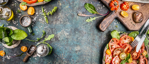 Foto Murales Healthy vegetarian salad making preparation with tomatoes on rustic background, top view, banner, copy space