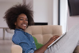 African American women at home in the chair using a laptop
