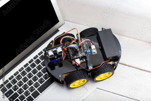 Poster robot on four wheels with a laptop on a wooden white table