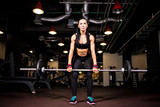 Muscular young fitness woman doing heavy deadlift exercise in gym
