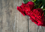 beautiful red roses on wooden background.