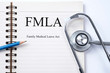 Stethoscope on notebook and pencil with  FMLA family medical lea
