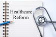 Stethoscope on notebook and pencil with  healthcare reform  word