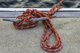 Red mooring rope tied off to cleat on dock
