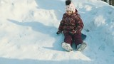 A little girl riding a snow hill in a Sunny cold winter day. Slow motion.