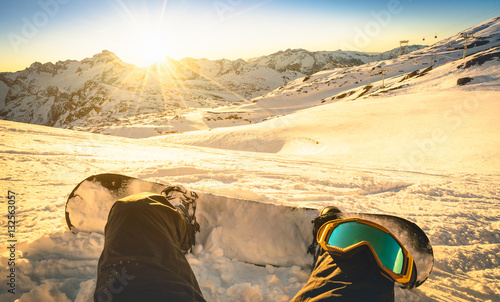 obraz lub plakat Snowboarder sitting on relax moment at sunset in french alps ski resort - Winter sport concept with person on top of the mountain ready to ride down - Legs view point with warm backlighting filter