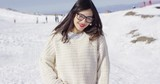 Half body portrait of beautiful smiling young woman in glasses on snow covered ski slope