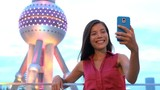 China Shanghai tourist taking selfie photo with smart phone by Oriental Pearl Tower at night. Happy young woman smiling and laughing having fun vacation travel at famous chinese tourist attraction.