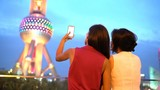 Shanghai China tourists taking photo with smart phone of Oriental Pearl Tower at night at famous chinese tourist attraction destination. Woman friends on travel taking having fun in China.