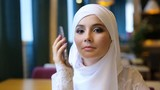 Young Muslim Girl Uses Smartphone In Cafe