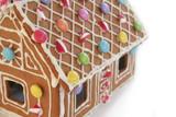 Casetta di pan di zenzero con dolci e caramelle su sfondo bianco. Dolce per Natale