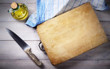 Cutting board, knife, cruet with extra virgin olive oil and dish towel on wooden background