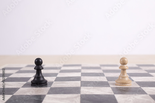 Poster black and white wooden pawns on chessboard