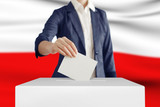 Voting. Woman putting a ballot into a voting box with Poland flag on background. - 132595019