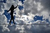 Woman silhouette balancing on rope