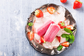 Homemade strawberry popsicles on metal plate with ice and berries. Summer food concept with copy space for text. Top view.