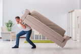 Man moving furniture at home