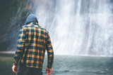 Fototapety Man walking at waterfall alone Travel Lifestyle adventure concept active vacations into the wild wearing cozy shirt and hat