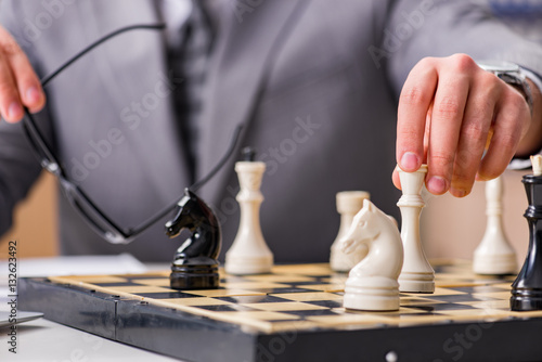 Fotografiet Young businessman playing chess in the office