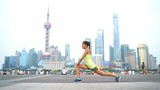 Runner stretching legs after workout in Shanghai, China on famous boardwalk with skyline. Urban city lifestyle. Active Asian woman training outside on the Bund doing leg exercises muscle stretches.