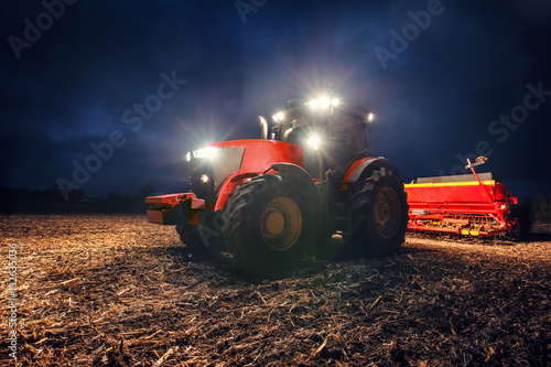 Tractor preparing land with seedbed cultivator at night Poster
