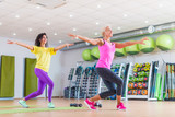 Two happy female fitness models dancing Zumba, doing aerobic exercises working out to lose weight in gym with colorful equipment in background