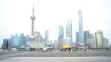 Asian woman running in city of Shanghai, China on famous boardwalk with skyline. Urban city lifestyle. Active woman runner exercising outside jogging on the Bund.