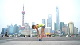 Yoga woman doing urban workout fitness on the Bund boardwalk, Shanghai city. Female yoga instructor doing sun salutation working out training with famous chinese skyline background.