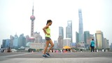 Fitness woman doing lunges exercising in Shanghai China. Girl doing front lunge bodyweight exercise outdoors on the Bund with famous Shanghai skyline in background. Mixed race Chinese Asian model.