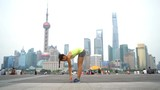 Yoga woman doing urban workout fitness on the Bund boardwalk, Shanghai city.