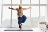 Confident tattooed man practicing yoga at home