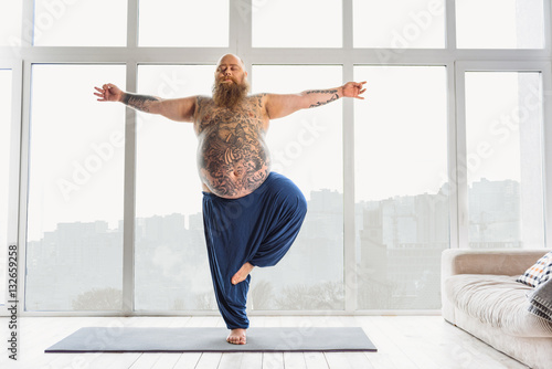 Confident tattooed man practicing yoga at home - 132659258