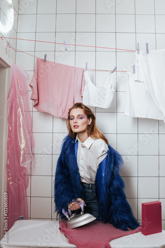 Poster Woman in fur coat ironing clothes in bathroom