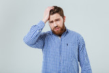 Sad bearded young man with hand on head having headache