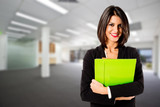 smiling business woman with green folder on office background