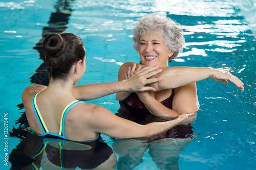 Starszy kobiety rozciąganie w basenie