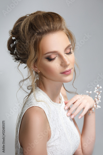 Pretty bride with beautiful elegant hairstyle, isolated on a gray background. © ksi