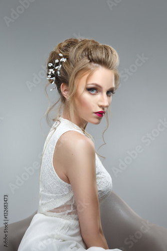 Elegant bride with a beautiful hairstyle and bright make-up isolated on a gray background. © ksi