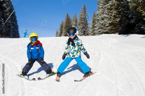 Poster Two young children, siblings brothers, skiing in Austrian mounta