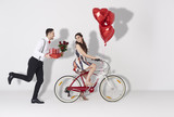 Fototapety Happy couple with gift and heart shaped balloon