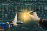Double exposure of Hand holding blank smart phone checking financial stats on screen for trading stock concept.