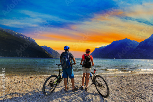 Poster Mountain biking, couple with bikes at sunset on Lake Garda, Riva